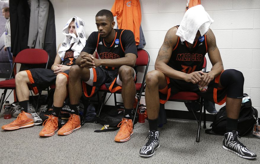 Mercer's Kevin Canevari, Darious Moten, and Jibri Bryan sit in the locker room after the second half of an NCAA college basketball third-round tournament game against Tennessee, Sunday, March 23, 2014, in Raleigh. Tennessee Won 83-63. (AP Photo/Chuck Burton)