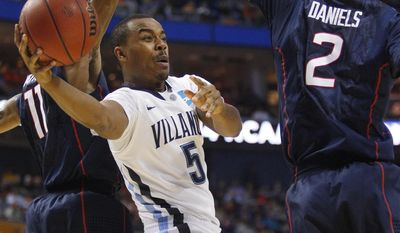 Villanova's Tony Chennault (5) passes between Connecticut's Ryan Boatright (11) and DeAndre Daniels (2) during the first half of a third-round game in the NCAA men's college basketball tournament in Buffalo, N.Y., Saturday, March 22, 2014. (AP Photo/Bill Wippert)