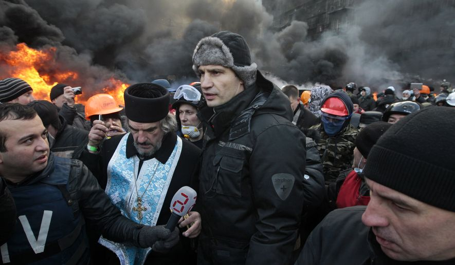 Opposition leader and former WBC heavyweight boxing champion Vitali Klitschko, center, addresses protesters near the burning barricades between police and protesters in central Kiev, Ukraine, Thursday Jan. 23, 2014.  Klitschko dove behind the wall of black smoke engulfing much of downtown Kiev on Thursday, pleading with both police and protesters to uphold the peace until the ultimatum, demanding that Yanukovych dismiss the government, call early elections and scrap harsh anti-protest legislation that triggered the violence. (AP Photo/Sergei Chuzavkov)