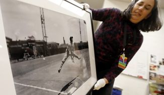"In this photo made on Monday, March 17, 2014, Louise Lippincott, the Curator of Fine Arts at the Carnegie Museum of Art, picks up a framed photograph made by Charles ""Teenie"" Harris at the museum in Pittsburgh. Harris made the image of New York Cubans' third baseman Horacio Martinez jumping over the base at Forbes Field in Pittsburgh in 1941.The museum is hosting an exhibit of photographs by Harris that opened on March 22 and runs through Sept. 22, 2014. It features a collection of Harris' work highlighting the golden years of Negro League baseball. The show features images of greats such as Jackie Robinson, Josh Gibson and documents the desegregation of local sandlot teams. (AP Photo/Keith Srakocic)"
