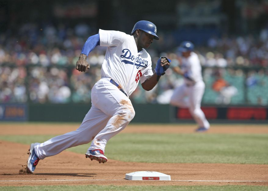 The Los Angeles Dodgers' Yasiel Puig rounds third on his way to scoring during the second game of the two-game Major League Baseball opening series between the Los Angeles Dodgers and Arizona Diamondbacks at the Sydney Cricket Ground in Sydney, Sunday, March 23, 2014. (AP Photo/Rick Rycroft)