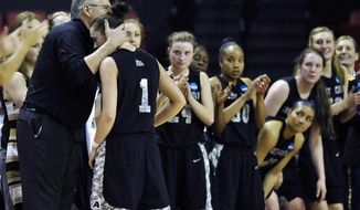 Army head coach Dave Magarity, left, hugs senior Jen Hazlett as she exits the game during the second half of the first round of the NCAA women's college basketball game against Maryland tournament on Sunday, March 23, 2014, in College Park, Md. Maryland won 90-52. (AP Photo/Gail Burton)
