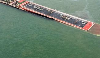 In this image provided by the U.S. Coast Guard a barge loaded with marine fuel oil sits partially submerged in the Houston Ship Channel, Saturday March 22, 2014. The bulk carrier Summer Wind, reported a collision between the Summer Wind and a barge, containing 924,000 gallons of fuel oil, towed by the motor vessel Miss Susan. The barge collided with a ship in Galveston Bay on Saturday, leaking an unknown amount of the fuel into the popular bird habitat as the peak of the migratory shorebird season was approaching. (AP Photo/U.S. Coast Guard, PO3 Manda Emery)