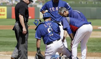 Texas Rangers catcher Geovany Soto, second from left, is examined by trainers and coaches during the second inning of a spring exhibition baseball game against the San Diego Padres, Sunday, March 23, 2014, in Surprise, Ariz. Soto was taken out of the game. (AP Photo/Darron Cummings)