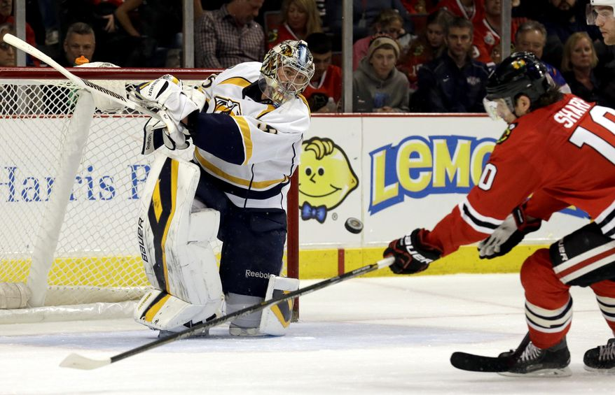 Nashville Predators goalie Pekka Rinne (35), left, blocks a shot by Chicago Blackhawks' Patrick Sharp (10) during the second period of an NHL hockey game in Chicago, Sunday, March 23, 2014. (AP Photo/Nam Y. Huh)