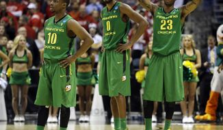 Oregon's Johnathan Loyd (10), Mike Moser (0) and Elgin Cook (23) react during the second half of a third-round game against the Wisconsin in the NCAA college basketball tournament Saturday, March 22, 2014, in Milwaukee. Wisconsin won 82-77. (AP Photo/Morry Gash)