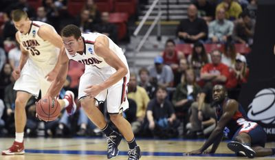 Arizona forward Aaron Gordon, center, grabs a loose ball as teamate center Kaleb Tarczewski, left, runs alongside and Gonzaga forward/center Sam Dower, right, looks on from the floor, right, during the second half of a third-round game in the NCAA college basketball tournament Sunday, March 23, 2014, in San Diego. (AP Photo/Denis Poroy)