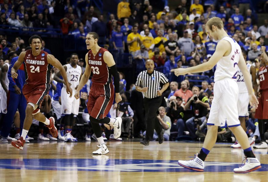 Stanford's Josh Huestis (24) and Dwight Powell (33) celebrate as Kansas' Conner Frankamp, right, heads toward the sideline at the end of a third-round game of the NCAA college basketball tournament Sunday, March 23, 2014, in St. Louis. Stanford won 60-57. (AP Photo/Jeff Roberson)