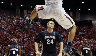 Arizona forward Aaron Gordon (11) dunks as Gonzaga center Przemek Karnowski (24) looks on during the first half of a third-round game in the NCAA college basketball tournament Sunday, March 23, 2014, in San Diego. (AP Photo/Lenny Ignelzi)
