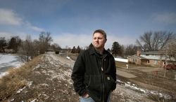 Brandon Nadeau stands on the earthen dike near his northeast Valley City, N.D. home in the 100-year floodplain on Thursday, March 20, 2014. Despite a bill signed by President Barack Obama on Friday, March 21, 2014, he will still see higher annual premiums. (AP Photo/Bruce Crummy)