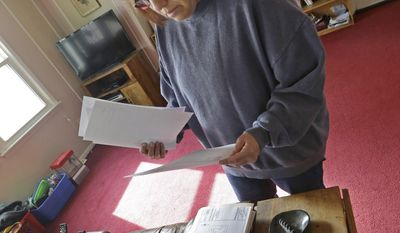Regina Bachman looks through papers dealing flood insurance on her property inside her home in Loveland, Ohio on Friday, March 21, 2014. Bachman bought the home in September 2013 and was initially told by the bank that flood insurance on the property would be affordable, only to find out after closing that the rates were going to increase over $7,000 more annually with new premiums for the National Flood Insurance Program. (AP Photo/Al Behrman)