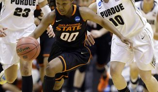 Oklahoma State guard Roshunda Johnson heads up court after making a steal in front of Purdue forward Liza Clemons (23) and guard Hayden Hamby (10) during the first half of a women's second round NCAA tournament college basketball game in West Lafayette, Ind., Monday, March 24, 2014.  (AP Photo/Michael Conroy)