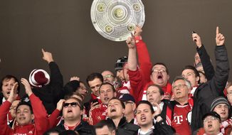 Bayern fans with a trophy celebrate during  the German Bundesliga soccer match between FSV Mainz 05 and Bayern Munich in Mainz,  Germany, Saturday, March 22, 2014. (AP Photo/Martin Meissner)