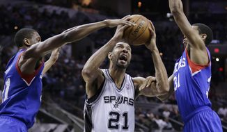 San Antonio Spurs' Tim Duncan (21) is pressured by 76ers' Thaddeus Young, left, and Hollis Thompson, right, during the first half of an NBA basketball game, Monday, March 24, 2014, in San Antonio. (AP Photo/Eric Gay)