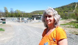 FILE - In this Monday, May 6, 2013, file photo, Vera Scroggins stands in front of a gas compressor station in Liberty Township in northwestern Pennsylvania. Scroggins, a  high-profile anti-fracking activist who often gives tours of natural gas drilling sites in northeastern Pennsylvania's Marcellus Shale region, asked a judge Monday, March 24, 2014, for relief from an order barring her from stepping foot on more than 300 square miles of land owned or leased by one of the state's leading natural gas drillers. Scroggins said the injunction, in place since October, has effectively prevented her from traveling to her favorite grocery store, eye doctor, hospital, restaurants, businesses and friends' homes because all of them have leased land to Cabot Oil & Gas Corp. (AP Photo/Mary Esch, File)