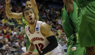 Wisconsin guard Traevon Jackson (12) drives to the basket against Oregon defense during the second half of a third-round game of the NCAA college basketball tournament Saturday, March 22, 2014, in Milwaukee. (AP Photo/Morry Gash)