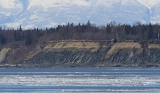 Two men enjoy the view and take pictures of Cook Inlet and Mount Susitna, also known as Sleeping Lady, from the edge of mudflats on Monday, March 24, 2014, in Anchorage, Alaska. Temperatures reached the mid-30s on Monday. Public safety officials warn against walking on the mudflats, which can be unstable if not frozen. (AP Photo/Dan Joling)