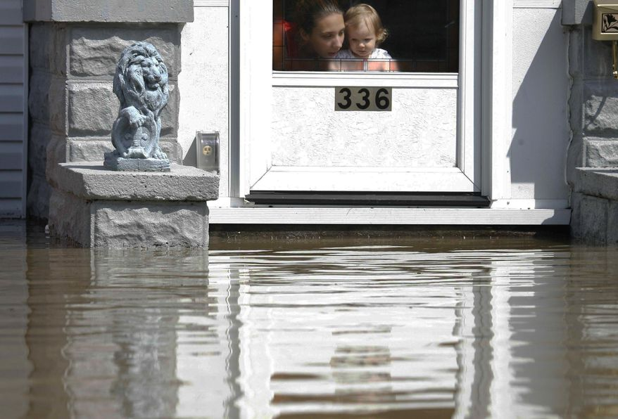 FILE - In this Wednesday, Aug. 22, 2007 file photo, a woman and a child look out of their front door at flood waters in Findlay, Ohio. Many home and business owners across Ohio with national flood insurance are likely to be hit with rate increases in 2014. Around 20,000 property owners in the state are among the 1.1 million policyholders nationwide facing higher rates to rescue the debt-ridden National Flood Insurance Program. (AP Photo/Madalyn Ruggiero)