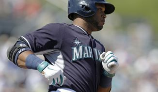 Seattle Mariners' Robinson Cano runs as he reaches on a field error by Chicago White Sox first baseman Jose Abreu during the third inning a spring exhibition baseball game Monday, March 24, 2014, in Peoria, Ariz. (AP Photo/Darron Cummings)