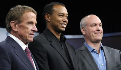 Tiger Woods, flanked by PGA Tour commissioner Tim Finchem, left and Quicken Loans Chief Executive Officer Bill Emerson, right, pose for a photo at the Newseum in Washington, Monday, March 24, 2014, after announcing that Quicken Loans had signed a multi-year agreement to become the title sponsor of the Quicken Loans National to be played at Congressional Country Club in Bethesda, Md., in June. (AP Photo/Susan Walsh)