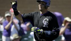 Colorado Rockies' Troy Tulowitzki celebrates a home run against the Kansas City Royals during the second inning of a spring exhibition baseball game in Scottsdale, Ariz., Monday, March 24, 2014. (AP Photo/Chris Carlson)