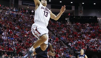 Arizona guard Nick Johnson, above, shoots above Gonzaga guard Gary Bell, Jr. during the first half of a third-round game in the NCAA college basketball tournament Sunday, March 23, 2014, in San Diego. (AP Photo/Lenny Ignelzi)
