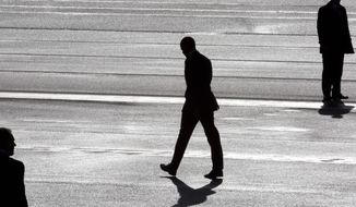 President Barack Obama, center, and two secret service agents are silhouetted as he walks toward Marine One helicopter upon arrival at Schiphol Amsterdam Airport, Netherlands, Monday March 24, 2014. Obama will attend the two-day Nuclear Security Summit in The Hague. (AP Photo/Peter Dejong, POOL)