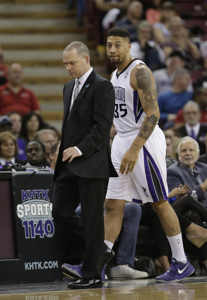 In this photo taken Friday, March 21, 2014, Sacramento Kings forward Royce White walks past Kings head coach Michael Malone  to enter his first NBA basketball game in the closing moments of the Kings 99-79 loss to the San Antonio Spurs in Sacramento, Calif.,  White was drafted by the Houston Rockets with the No. 16 pick in the 2012 draft but spent his rookie season in a dispute with the team over how to treat his anxiety disorder which includes a fear of flying. Not only must he prove he can still play, White, who is on his second 10 day contract with Kings, has to show he can handle the rigors of the league's schedule including his first road trip this week.(AP Photo/Rich Pedroncelli)