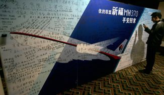 """A man uses his mobile phone near a board with the characters """"Pray for MH370 safe return"""" meant for relatives and workers to write their prayers and well wishes on in a room reserved for relatives of Chinese passengers aboard the missing Malaysia Airline jet in Beijing, China, Monday, March 24, 2014. Rain was expected to hamper the hunt Monday for debris suspected of being from the missing Malaysia Airlines jet, as the United States prepared to move a specialized device that can locate black boxes into the south Indian Ocean region.  (AP Photo/Ng Han Guan)"""