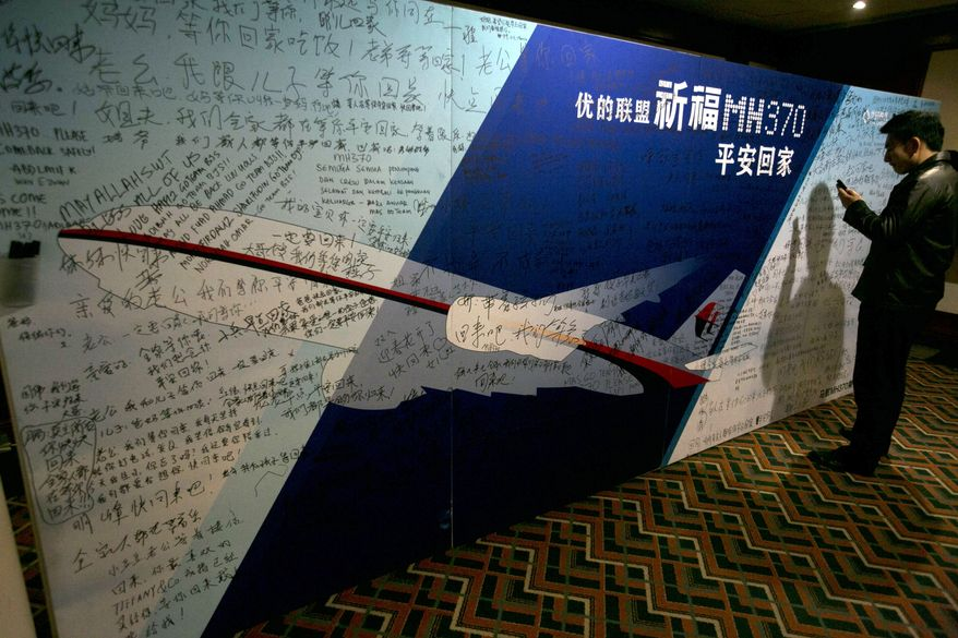 "A man uses his mobile phone near a board with the characters ""Pray for MH370 safe return"" meant for relatives and workers to write their prayers and well wishes on in a room reserved for relatives of Chinese passengers aboard the missing Malaysia Airline jet in Beijing, China, Monday, March 24, 2014. Rain was expected to hamper the hunt Monday for debris suspected of being from the missing Malaysia Airlines jet, as the United States prepared to move a specialized device that can locate black boxes into the south Indian Ocean region.  (AP Photo/Ng Han Guan)"