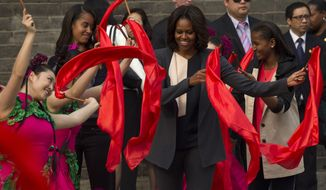 U.S. first lady Michelle Obama, center, dances with performers during her visit to an ancient city wall with her daughters Malia, second from left, and Sasha, right, in Xi'an, in northwestern China's Shaanxi province, Monday, March 24, 2014. (AP Photo/Alexander F. Yuan)