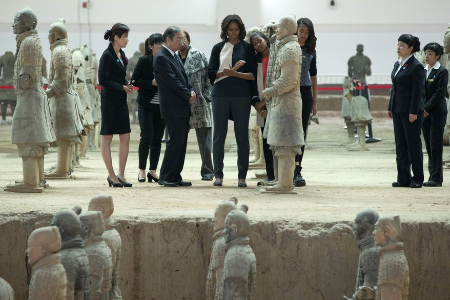 U.S. first lady Michelle Obama, center, checks a terracotta warrior as she visits Qinshihuang Terracotta Warriors and Horses Museum with her daughters, Malia, third right, and Sasha, fourth right, and her mother, Marian Shields Robinson, fourth left, in Xi'an, in northwestern China's Shaanxi province, Monday, March 24, 2014. (AP Photo/Alexander F. Yuan)