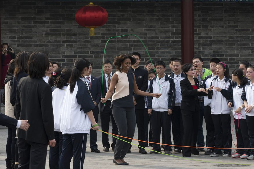 U.S. first lady Michelle Obama, center, jumps rope with Chinese schoolchildren as she visits an ancient city wall with her daughters and her mother in Xi'an, in northwestern China's Shaanxi province, Monday, March 24, 2014. (AP Photo/Alexander F. Yuan)
