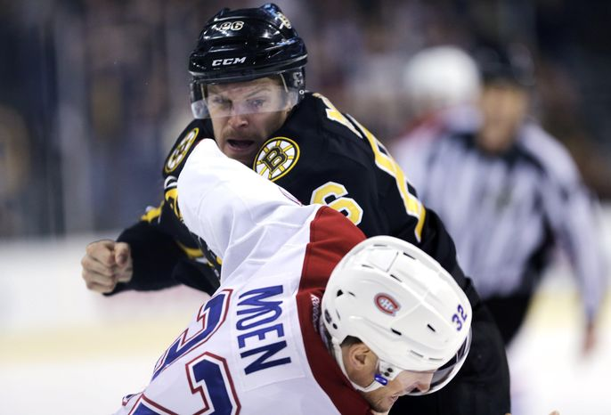 Boston Bruins defenseman Kevan Miller fights eiyh Montreal Canadiens left wing Travis Moen (32) during the first period of an NHL hockey game, Monday, March 24, 2014, in Boston. (AP Photo/Charles Krupa)