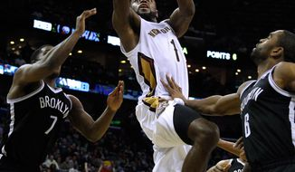 New Orleans Pelicans forward Tyreke Evans (1) drives to the basket against Brooklyn Nets guard Joe Johnson (7) and Brooklyn Nets forward Alan Anderson (6) during the second half of an NBA basketball game in New Orleans, Monday, March 24, 2014. The Pelicans won 109-104. (AP Photo/Jonathan Bachman)