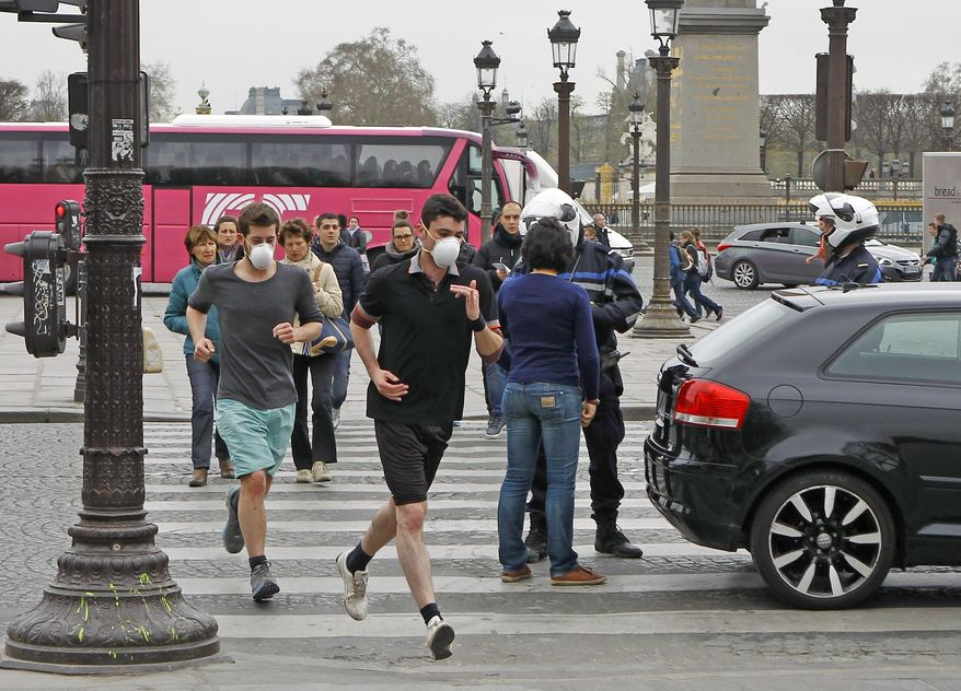 FILE - In this Monday, March 17, 2014 file photo, two joggers wearing protective masks run past a police officer controlling a vehicle on the Concorde square in Paris. Air pollution kills about 7 million people worldwide every year according to a new report from the World Health Organization published Tuesday March 25, 2014. The agency said air pollution triggers about 1 in 8 deaths and has now become the single biggest environmental health risk, ahead of other dangers like second-hand smoke. (AP Photo/Remy de la Mauviniere, File)