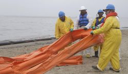 An oil spill clean up crew drags a boom along East Beach in Galveston, Texas, Monday, March 24, 2014. Thousands  of gallons of tar-like oil spilled into the major U.S. shipping channel after a barge ran into a ship Saturday. (AP Photo/Pat Sullivan)