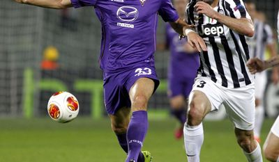 Fiorentina's Mario Gomez, left, is chased  by Juventus' Giorgio Chiellini during an Europa League, round of 16, return-leg soccer  match between Fiorentina and Juventus, at the Artemio Franchi stadium in Florence, Italy, Thursday,  March 20, 2014. (AP Photo/Fabrizio Giovannozzi)
