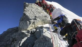 ** FILE ** In this image released by mountain guide Adrian Ballinger of Alpenglow Expeditions and taken Saturday, May 18, 2013, climbers navigate the Hillary Step just below the summit of Mount Everest, in the Khumbu region of the Nepal Himalayas. (AP Photo/Alpenglow Expeditions, Adrian Ballinger)