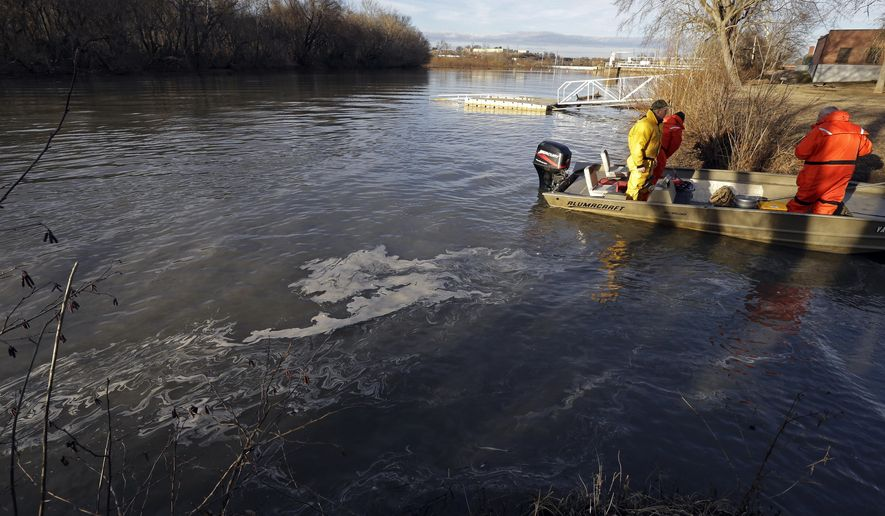 FILE - This Wednesday Feb. 5, 2014 file photo shows state and federal officials dock after collecting sediment samples as coal ash surfaces on the water on the Dan River in Danville, Va. A coal ash spill from a break in a 48-inch storm water pipe at the Dan River Power Plant in Eden N.C. on Sunday released  up to 82,000 tons of ash according to Duke Energy. (AP Photo/Gerry Broome)