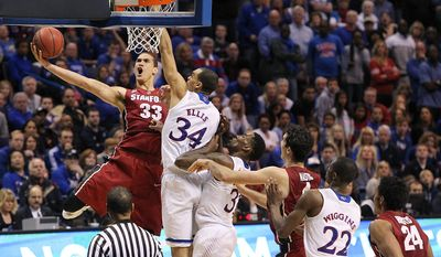 Stanford forward Dwight Powell drives to the basket against Kansas forward Perry Ellis in second half action during a Third Round NCAA Tournament game between Kansas and Stanford on Sunday, March 23, 2014, at the Scottrade Center in St. Louis.  (AP Photo/St. Louis Post-Dispatch, Chris Lee)