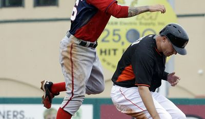 Washington Nationals' Jeff Kobernus, left, jumps over Miami Marlins' Jeff Baker after throwing to first base as Casey McGehee grounds into a double play in the fifth inning of an exhibition spring training baseball game, Monday, March 24, 2014, in Jupiter, Fla. (AP Photo/David Goldman)