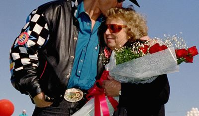 FILE - In this Nov. 15, 1992, file photo, NASCAR driver Richard Petty, left, kisses his wife, Lynda, during ceremonies before the start of the final race of his career, the Hooters 500, at Atlanta Motor Speedway in Hampton, Ga. Lynda died Tuesday, March 25, 2014, at her home in Level Cross, N.C., after battling cancer for several years. She was 72. (AP Photo/Ric Feld, File)
