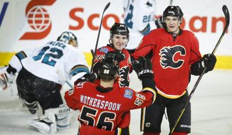 Calgary Flames' Joe Colborne, right, celebrates his goal with teammate Tyler Wotherspoon, left, and Curtis Glencross as San Jose Sharks goalie Alex Stalock picks himself up during second period NHL hockey action in Calgary, Monday, March 24, 2014. (AP Photo/The Canadian Press, Jeff McIntosh)