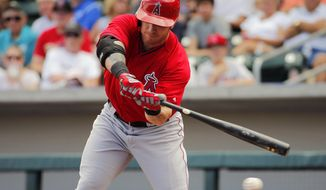 Los Angeles Angels' Josh Hamilton swings against the Chicago Cubs' during the first inning of a spring training baseball game, Tuesday, March 25, 2014, in Mesa, Ariz. (AP Photo/Matt York)