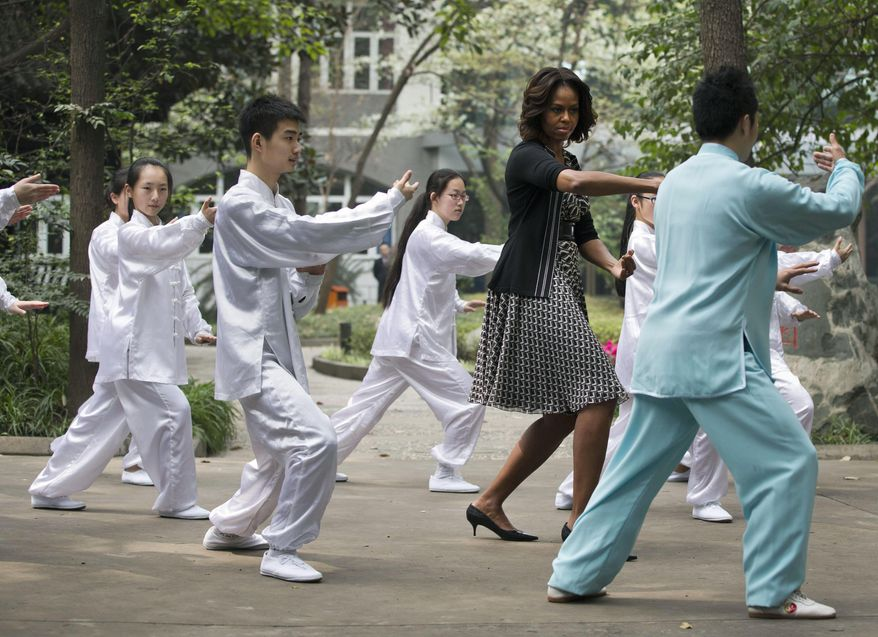 U.S. first lady Michelle Obama practices tai chi with students at Chengdu No.7 High School in Chengdu in southwest China's Sichuan province Tuesday, March 25, 2014. (AP Photo/Andy Wong)