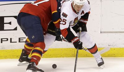 Florida Panthers defenseman Colby Robak (47) and Ottawa Senators right wing Chris Neil (25) battle for the puck during the second period of an NHL hockey game, Tuesday, March 25, 2014 in Sunrise, Fla. (AP Photo/Wilfredo Lee)