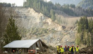 Rescue workers remove one of a number of bodies from the wreckage of homes destroyed by a mudslide near Oso, Wash., Monday, March 24, 2014. The search for survivors of Saturday's deadly mudslide grew Monday to include scores of people who were still unaccounted for as the death toll from the wall of trees, rocks and debris that swept through the rural community rose to at least 14. (AP Photo/seattlepi.com, Joshua Trujillo)