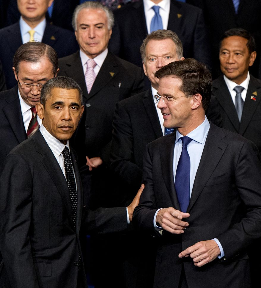 U.S. President Barack Obama, left, and Dutch Prime Minister Mark Rutte, right, pose for a group photo on the last day of the Nuclear Security Summit (NSS) in The Hague, Netherlands, Tuesday, March 25, 2014, with U.N. Secretary General Ban Ki-moon, top left, Brazil's Vice President Michel Temer, top center, Finland's President Sauli Niinisto, and Philippines Vice President Jejomar Binay. (AP Photo/Robin van Lonkhuijsen, Pool)
