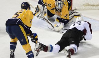 Nashville Predators goalie Pekka Rinne (35), of Finland,  gloves a shot by Colorado Avalanche left wing Jamie McGinn (11) as he is defended by forward Viktor Stalberg (25), of Sweden, in the second period of an NHL hockey game on Tuesday, March 25, 2014, in Nashville, Tenn. (AP Photo/Mark Zaleski)